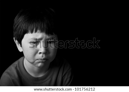 Cute young asian boy with serious look on black background in black and white
