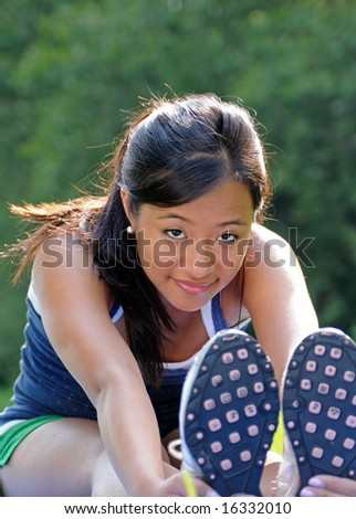 Cute Young Asian woman smiling while stretching - stock photo