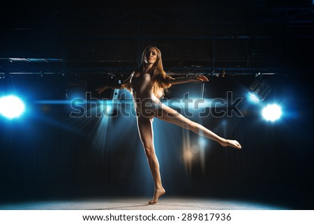 Cute young blonde ballerina dancing on stage in theater