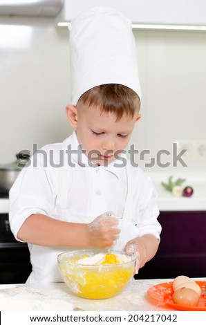Cute young boy baking a cake breaking eggs into a mixing bowl with flour in his apron and chefs toque as he adds the ingredients for the cake - stock photo