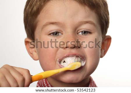 cute young boy brushing teeth with positive expression - stock photo