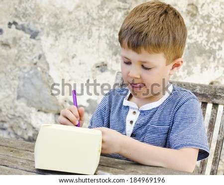 Cute young boy concentrating whilst making an Easter basket - stock photo