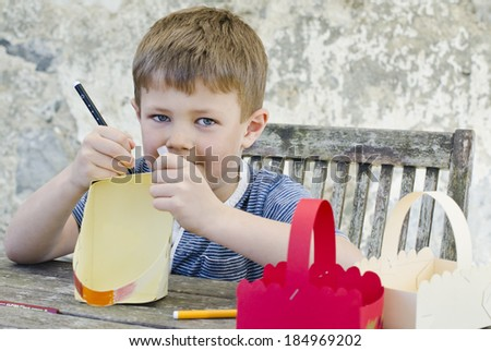Cute young boy decorating an Easter basket for an Easter egg hunt - stock photo