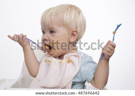 Cute young boy feeding himself with messy face, white background