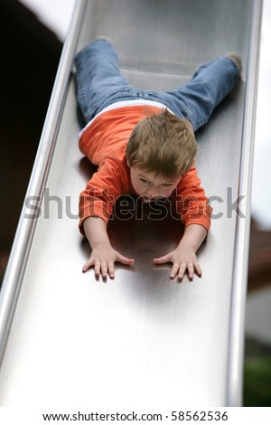 cute young boy going down a slide - stock photo