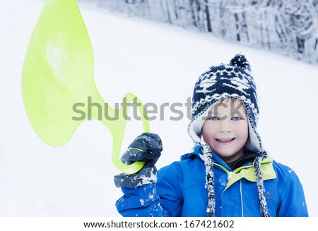 Cute, young boy holding up a sledge in the snow - stock photo