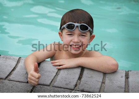 cute young boy in a swimming pool - stock photo