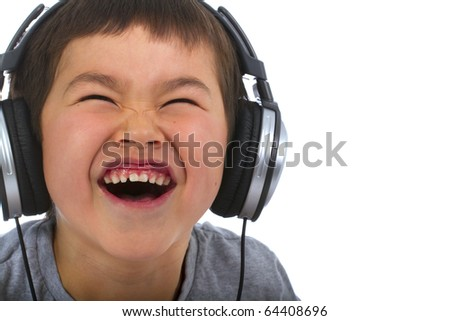 cute young boy listening to music and laughing - stock photo