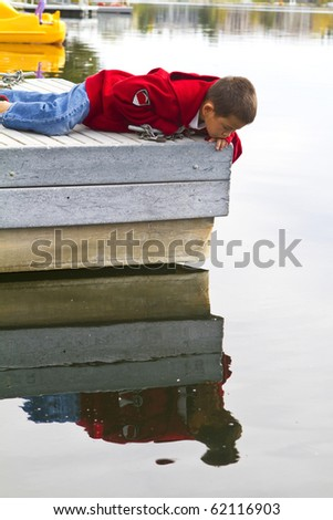 Cute young boy looking into the water off a dock with reflection - stock photo