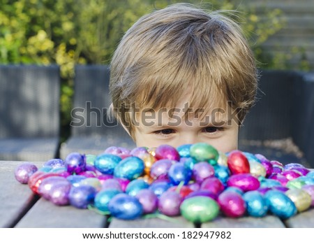 Cute young boy peering over a table looking at a big pile of chocolate Easter eggs - stock photo