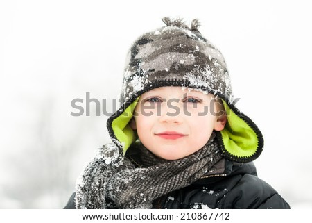 Cute young boy playing in snow - stock photo