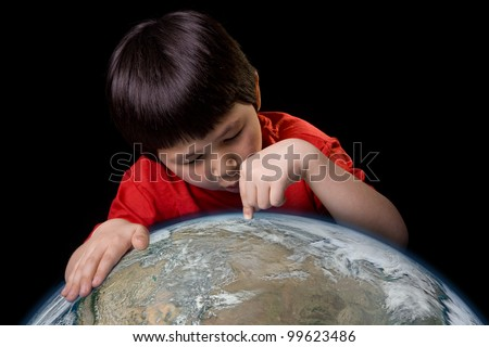Cute young boy pointing to a spot on planet earth with space background. Elements of this image furnished by NASA. - stock photo