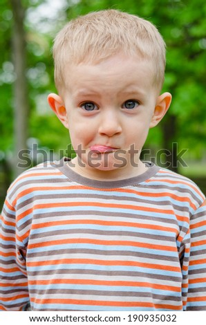 Cute young boy pulling a funny expression puckering up his lips with a look of amusement in his eyes - stock photo