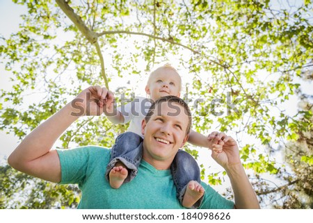 Cute Young Boy Rides Piggyback On His Dads Shoulders Outside at the Park. - stock photo