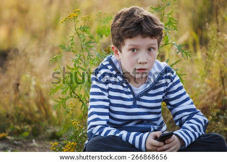Cute young boy with a mobile phone outdoor - stock photo