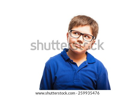 Cute young boy with glasses looking up towards copy space - stock photo