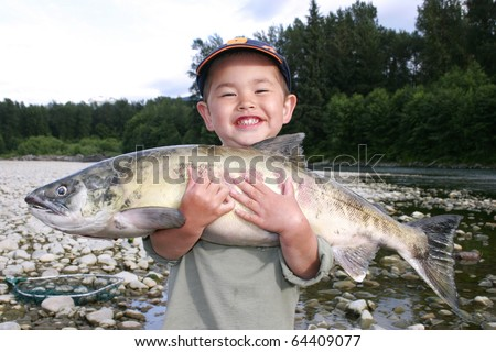 Cute young boy with great smile holding large salmon out fishing on a river - stock photo