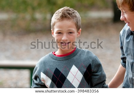 Cute young boy with smile on face, wearing sweater outdoors. - stock photo