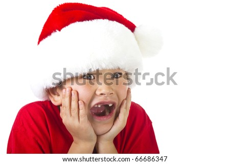 Cute young boy with two front teeth missing wearing a Christmas Santa hat with surprised expression isolated on white background