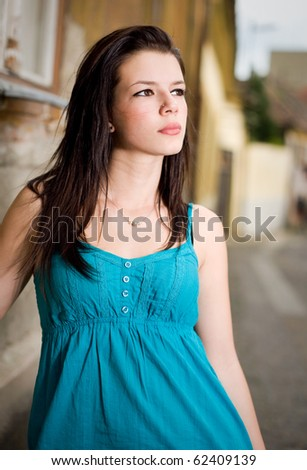 Cute young brunette posing on the street in blue dress.