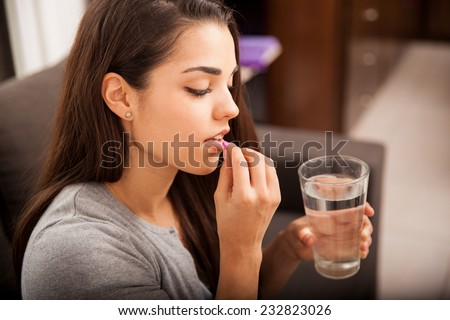 Cute young brunette taking a pill with a glass of water at home - stock photo