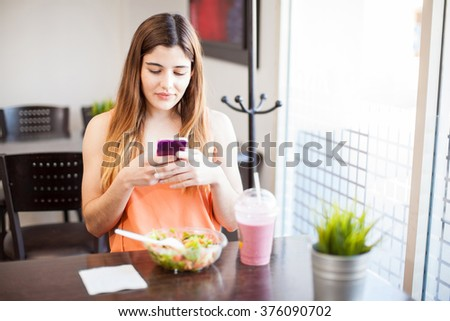 Cute young brunette using a smartphone to send a text while eating a healthy lunch in a restaurant - stock photo