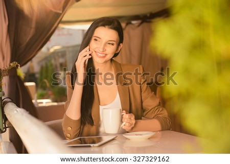 Cute young business woman in a cafe drinking tea and talking on the phone