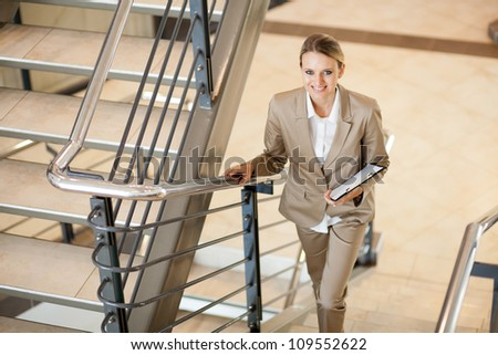 cute young businesswoman walking up stairs - stock photo