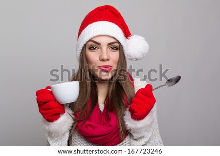 Cute young  Caucasian brunette Santa girl with coffee cup looking at camera making funny facial expression against gray background. Copy space available. - stock photo