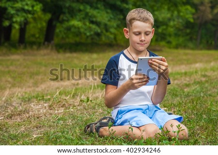 Cute young caucasian kid with freckles on his face in blue shorts and white and blue T-shirt and tablet and working in park and smiling. sitting and looking at display with smile. - stock photo