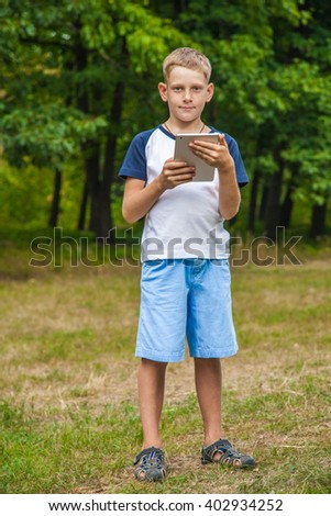 Cute young caucasian kid with freckles on his face in blue shorts and white and blue T-shirt and tablet and working in park and smiling. standing and looking at camera. - stock photo