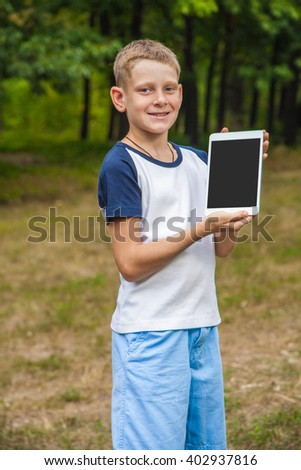 Cute young caucasian kid with freckles on his face in blue shorts and white and blue T-shirt and tablet and working in park and smiling. looking at camera with smile and showing display. - stock photo