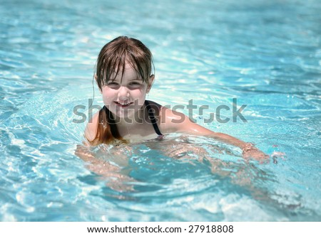 Cute Young Child Swimming in a Pool on a Sunny Day