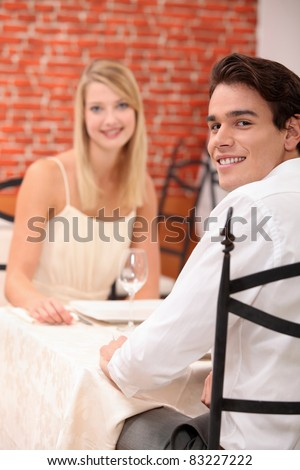 cute young couple at restaurant - stock photo