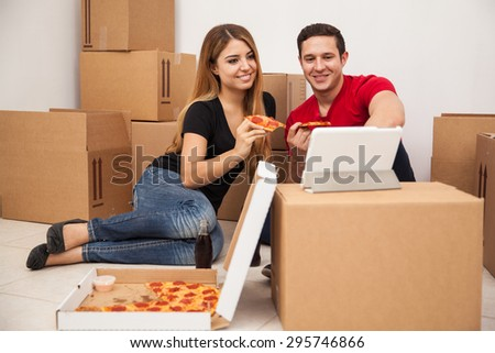 Cute young couple eating pizza and watching a TV show on a tablet computer while moving into their new home - stock photo