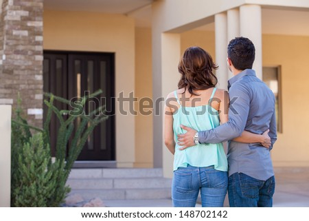 Cute young couple holding each other and looking at their new house - stock photo