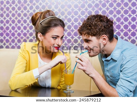 Cute young couple sitting at the table sharing a drink  - stock photo