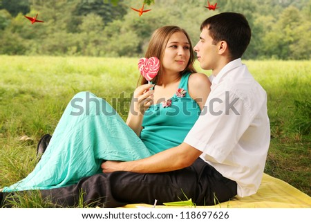 Cute young couple talking on the grass - stock photo