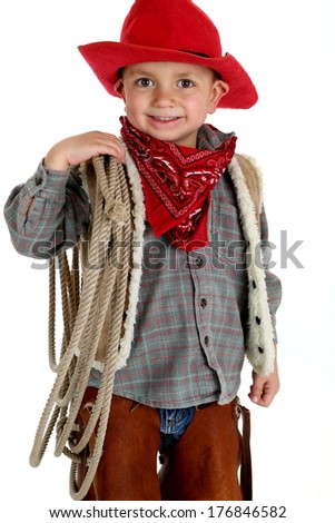 Cute young cowboy holding a rope smiling - stock photo