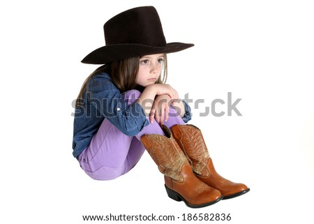 cute young cowgirl sitting with knees up