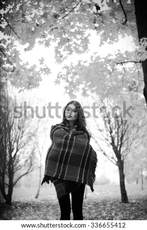 Cute young  dreaming woman with beautiful face and hair in warm plaid in autumn forest.Black and white