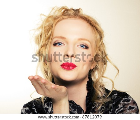 Cute young female blowing a kiss at you