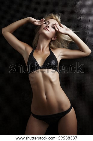 cute young female in lingerie posing on a dark background - stock photo