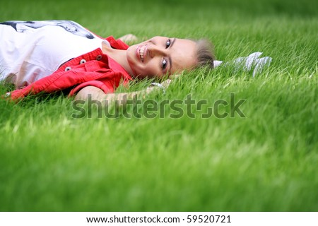 Cute young female lying on grass field at the park - stock photo