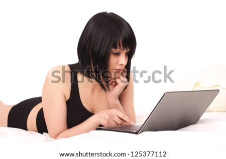 Cute young female lying with laptop in the bed - stock photo