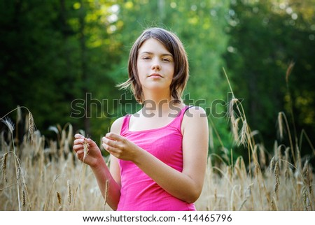 Cute young female stands in crop field holding flower - stock photo