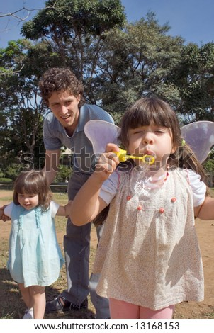 Cute young girl blowing bubbles while her younger sister and father look on. Vertically framed shot. - stock photo