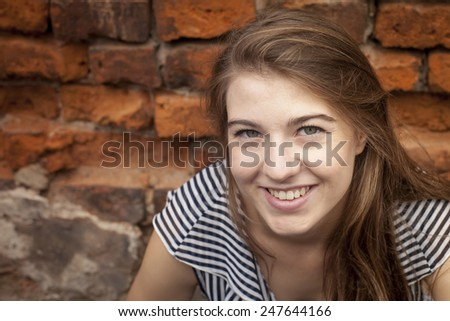 Cute young girl close-up portrait near a brick wall. - stock photo