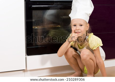 Cute young girl cook giving a thumbs up of success as she squats in front of the oven watching her homemade pizza cook - stock photo