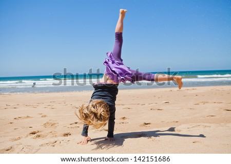 Cute young girl doing cartwheel in sand at beach with blue sky and ocean in background - stock photo